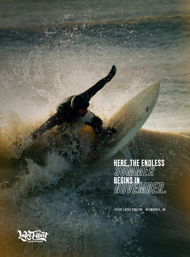"""A poster of a man surfing on Lake Michigan. The poster reads """"Here the endless summer begins in November."""""""