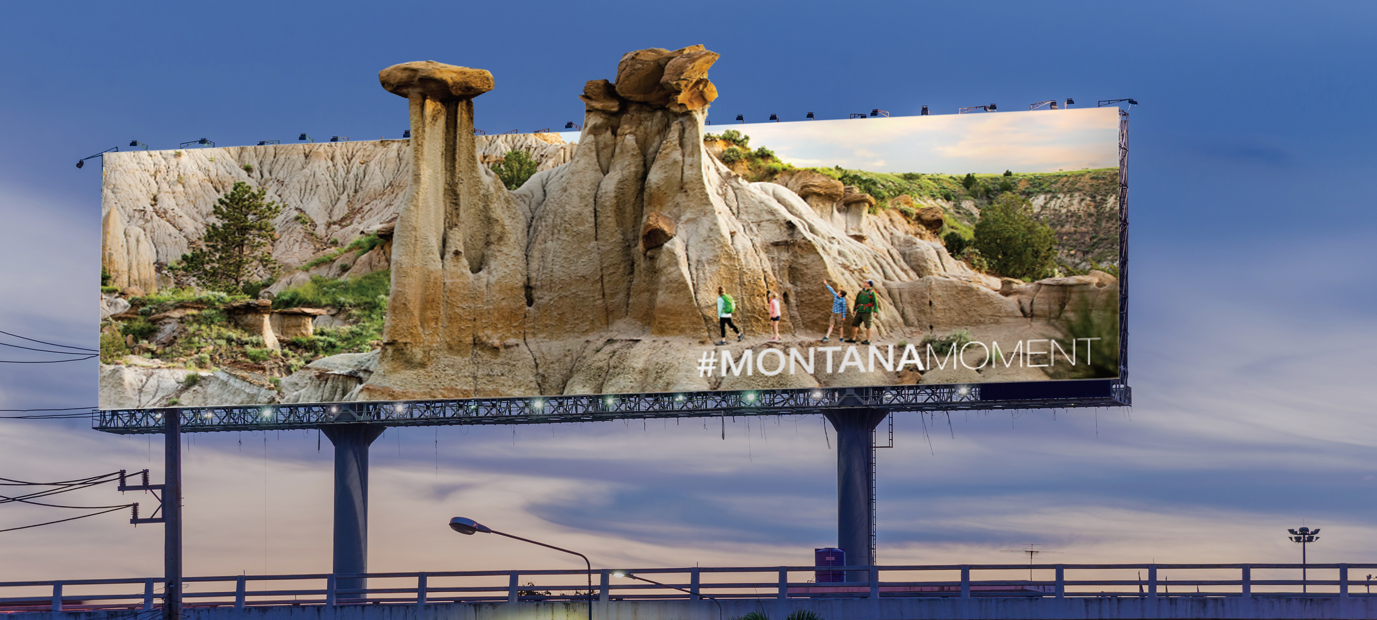 """Montana Tourism billboard featuring a family hiking near rock formations and text that reads: """"#MontanaMoment"""""""