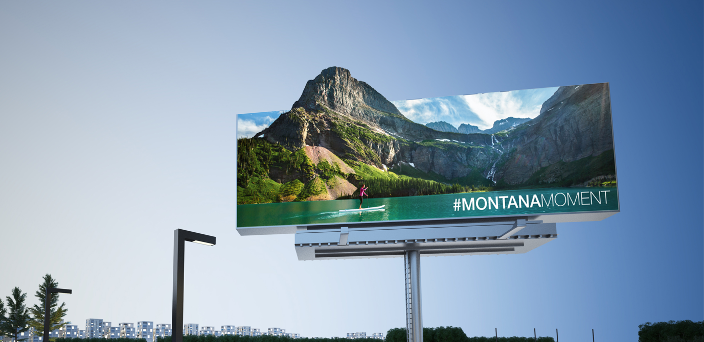 """Montana Tourism billboard featuring a mountain scene and text that reads: """"#MontanaMoment"""""""