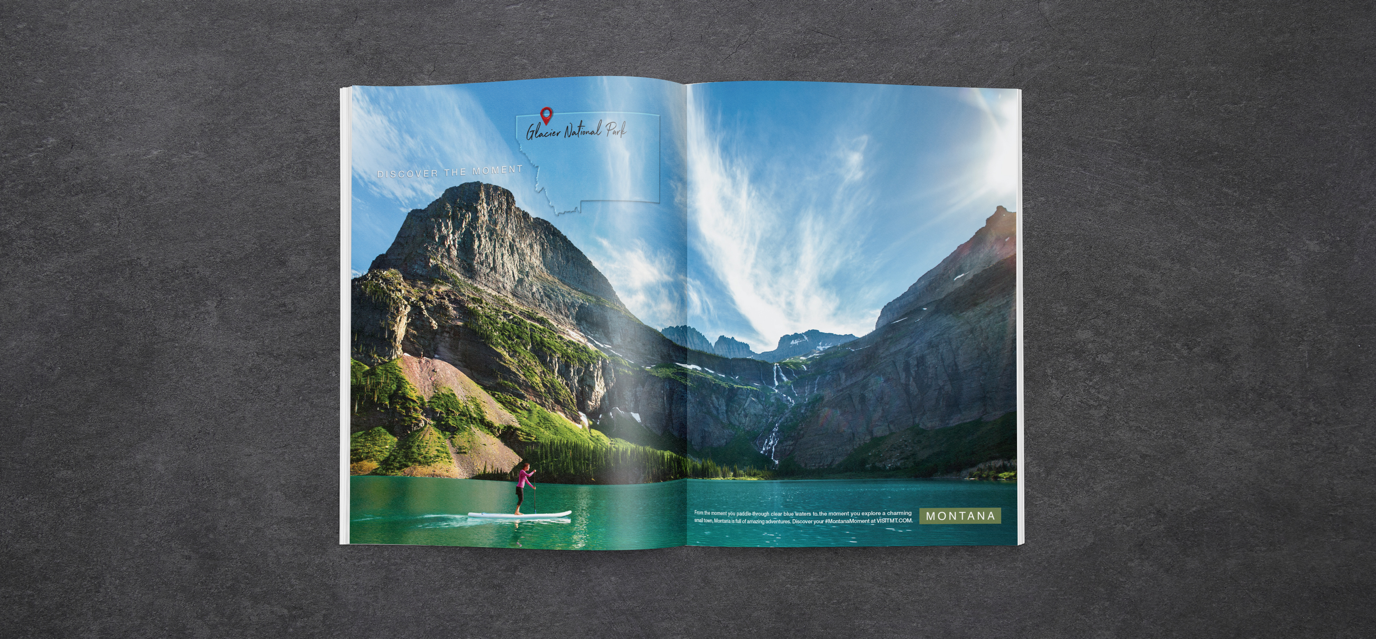 Montana Tourism full magazine spread featuring a woman stand-up paddle boarding on the water in Glacier National Park.