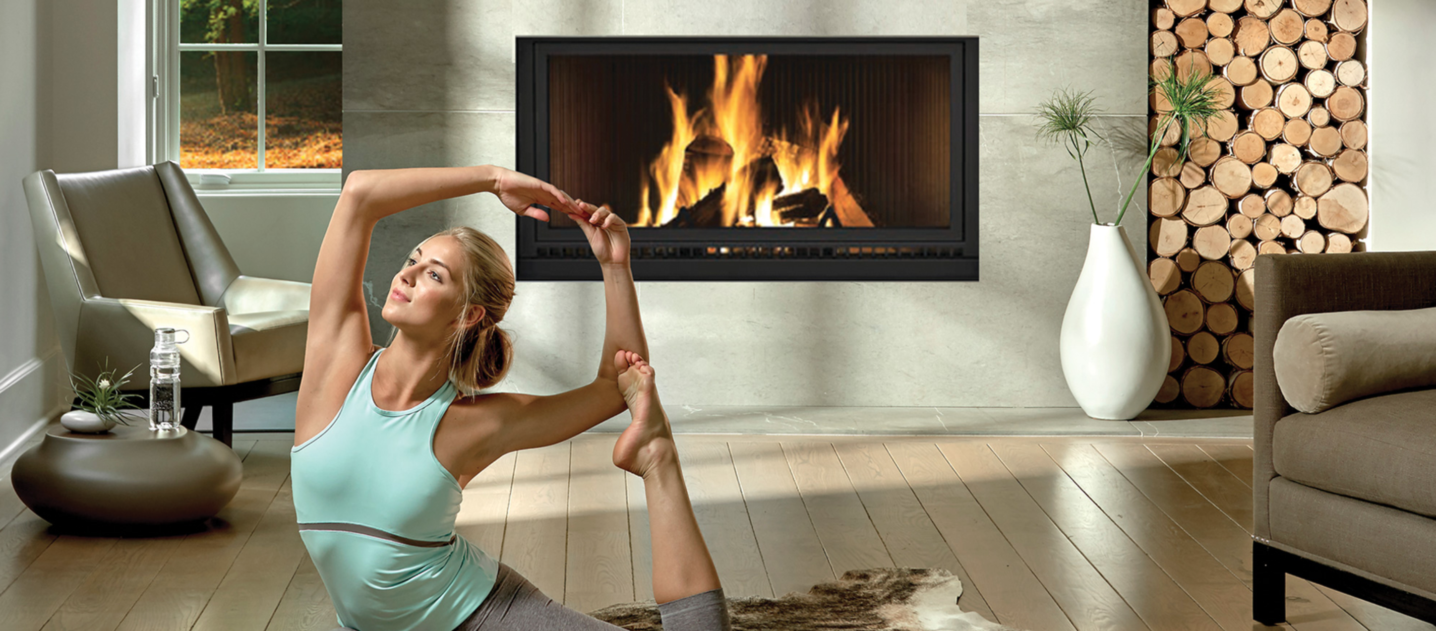 A woman in a yoga pose in front of a Napoleon fireplace.