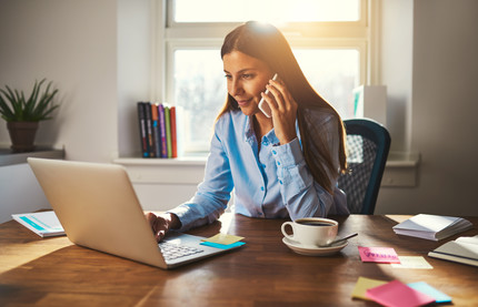 Woman talking on cell phone, on laptop working from home